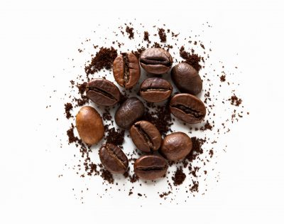 coffee beans and scattered ground coffee on white background