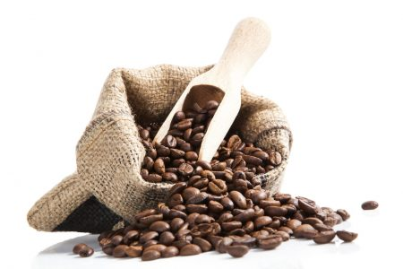 coffee beans on brown bag with wooden spoon isolated on white background. Culinary aromatic coffee drinking.